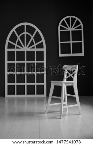 White chair on dark background.The wall is decorated with details in the form of arched doors and arched Windows. #1477541078