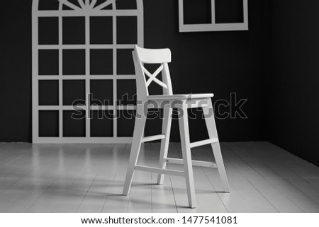 White chair on dark background.The wall is decorated with details in the form of arched doors and arched Windows. #1477541081