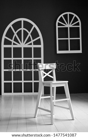 White chair on dark background.The wall is decorated with details in the form of arched doors and arched Windows. #1477541087