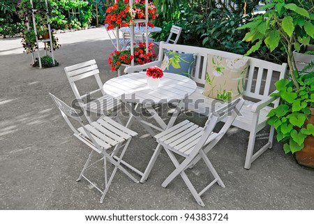 White chair, table, bench with pillows in a lush garden.