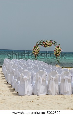 White chairs await guests at a beautiful beachside wedding in Mexico