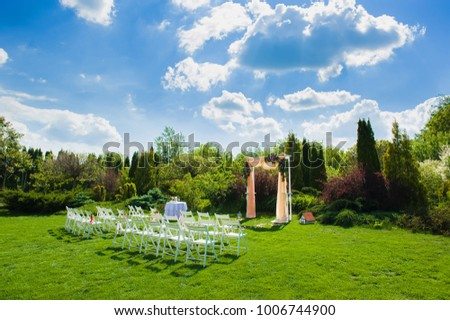 White chairs in front of beautiful wedding arch