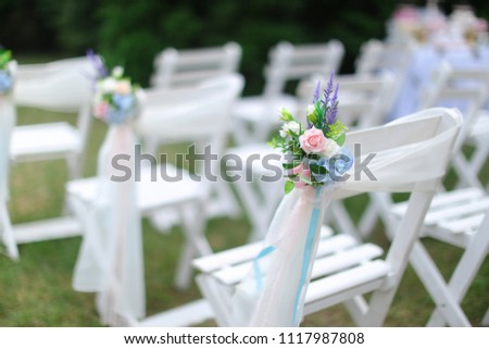 White chairs on green grass background, blurred photo. Concept of wedding seating places.