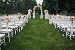 White chairs stand in the rows before wedding altar with pink flowers