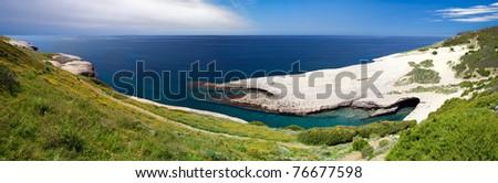 white chalk cliffs eroded coastline blue sky and sea at Caterina di Pittinuri Sardinia Italy beautiful summer panorama landscape and seascape impressive geologic rock formation - stock photo