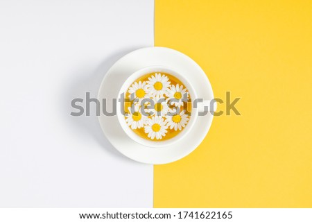 White chamomiles, cup of tea on yellow and white background. Herbal tea of chamomile flower. Chamomile tea concept. Flat lay, top view, copy space