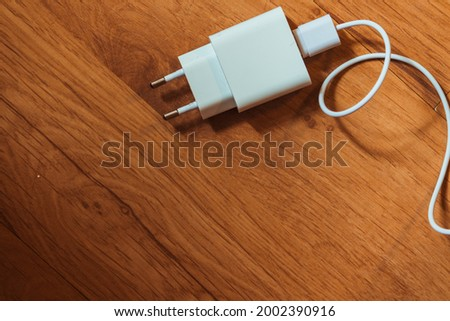 White charger with cable on a wooden background.  Stockfoto ©