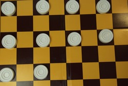 White checkers on black cells. Chess board with checkers, top view. White checkers are scattered on the chessboard.