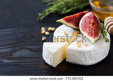 White cheese brie or camembert. Gourmet appetizer cheese plate with white cheese, figs, thyme, honey and nuts