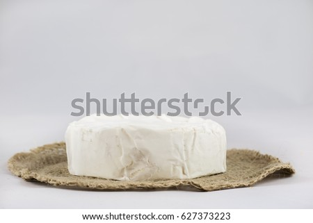 White cheese on a chopping board, white isolated background