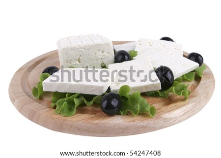 white cheese on wooden plate with olives
