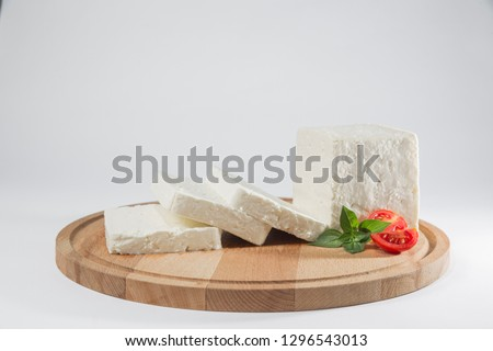White cheese with some garnitures such as lettuce, cherry tomato slice and basil on a wooden plate, white background Stok fotoğraf ©