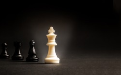 White chess king standout from all the blurred black chess , Leader can make an impact and different idea concept