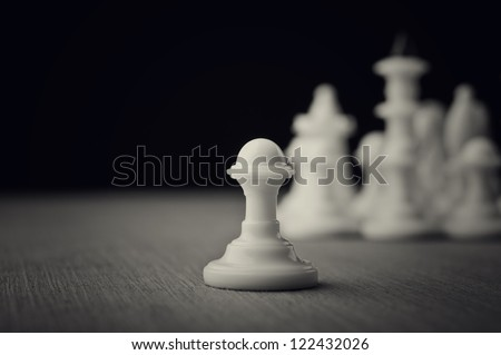 white chess pawns on wooden table