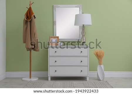 White chest of drawers with decor, coat stand and mirror in hallway. Interior design Foto d'archivio ©