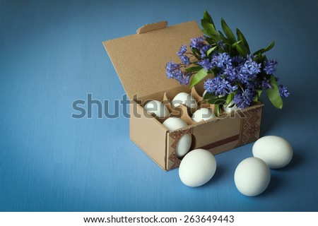 White chicken eggs in an egg box with flowers (Scilla) on a blue wooden background