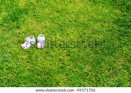 white children's sandals on a sunny green lawn