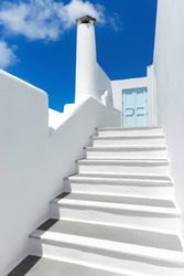 White chimney stack near a light blue door at the top of a staircase in Santorini Greece.