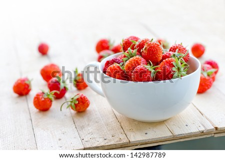 White china bowl filled with succulent juicy fresh ripe red strawberries on wooden  table top
