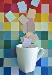 White china coffee / tea cup against an abstract textured background. Rainbow coloured  grid mosaic collage of coloured tiles squares / rectangles. Additional tiles coming out of the cup like steam