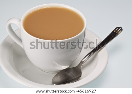 White china cup of tea with milk and teaspoon on a plain background - stock photo