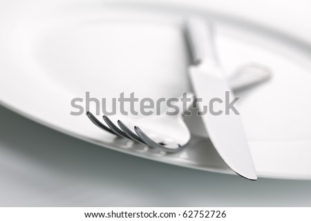 White china plate with crossed silver knife and fork cutlery, shallow deep of field with focus on tip of fork