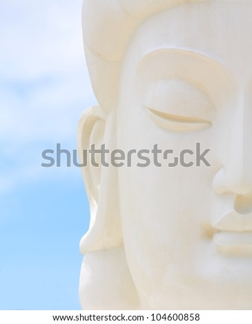 white chinese style buddha face with blue sky.