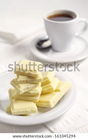 White chocolate and cup of coffee on table