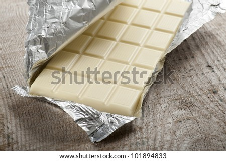 white chocolate bar in aluminum foil, on wood table