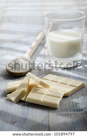 white chocolate bar with sugar and glass of milk, on wooden table lighted by the sun