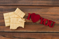 White chocolate pieces and inscription I love you. Chocolate bars and romantic message on wooden background.