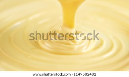 White Chocolate. Pouring melted liquid premium milk white chocolate. Close up of molten liquid hot chocolate swirl. Confectionery. Confectioner prepares dessert, icing