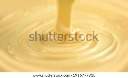 White Chocolate. Pouring melted liquid premium milk white chocolate. Close up of molten liquid hot chocolate swirl. Confectionery. Confectioner prepares dessert, icing.