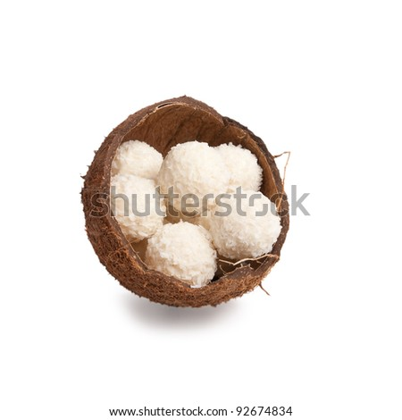 white chocolate truffles in a box of coconut halves isolated on white background