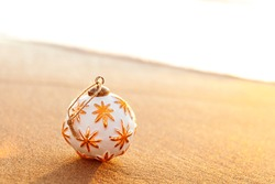 White Christmas ball on sandy beach at golden sunset in California with copy space on the right, season holiday concept - Image