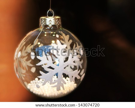White Christmas ball, with snow flakes decoration, over blurred background