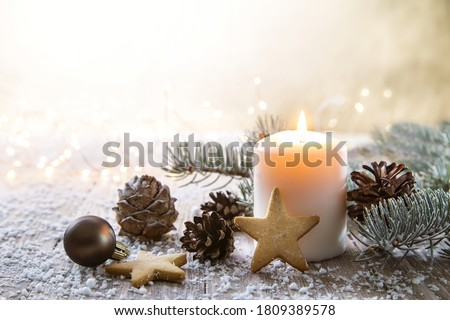 White Christmas candle on rustic wooden boards - Decoration with natural elements, twigs, pine cones and cookies. stock photo