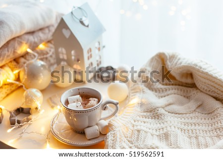 White Christmas decor: warm sweater, cup of hot cocoa with marshmallow and led string lights. Winter mood, holiday decoration.