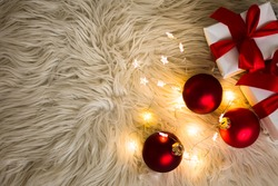 White Christmas gift boxes with red ribbon and Christmas balls and lights on furry blanket. Flat lay. Top view Christmas congratulations concept, copy space.