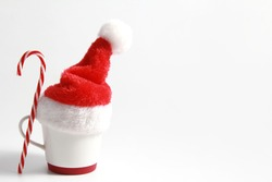 White Christmas mug in a Santa Claus hat, with a Lollipop on a white background. The concept of a cozy Christmas. Creative idea for cafes and coffee shops. Side view. Copy space.