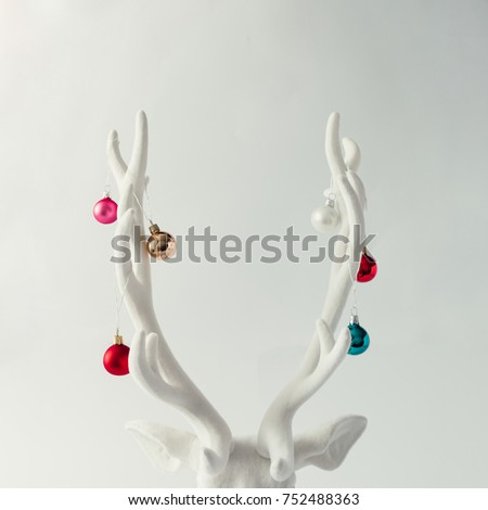 Shutterstock White Christmas reindeer head with antlers with christmas baubles. New Year concept.