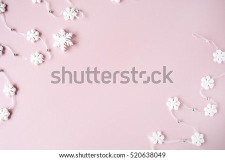 white christmas snowflakes decoration on pink background. christmas wallpaper. flat lay, top view