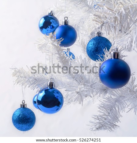 White Christmas tree branch with royal blue ornaments. Christmas greeting background. #526274251