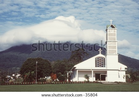White church in front of a mountain hidden in clouds