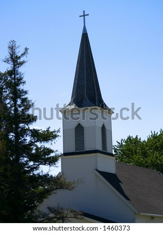 White church steeple with blue sky and background trees