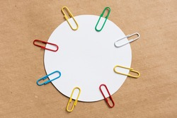 white circle with colored paper clips. Brown background from kraft paper. Blank template for text, copy space