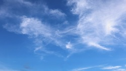 White cirrus clouds scattered in the sky. Streaks of white clouds lightly lit up the blue sky. selective focus