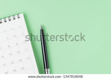 White clean calendar with black pen on pastel green background with copy space using as reminder, schedule, meeting agenda and work planning concept.