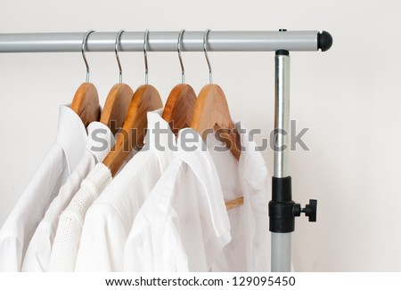 White clean clothes, shirts and jackets hanging on a rack in a row