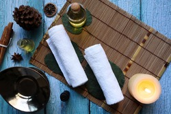 white clean cotton spa towel cloths prepared for day spa service on blue wooden table with massage oil bottle, essential oil, candle, and oil burner with background of vintage wooden wall in nice spa
